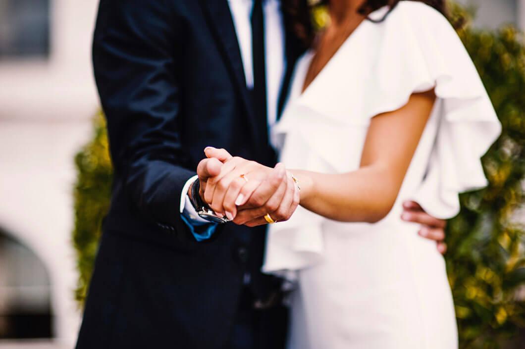 bröllopsparet visar ringarna